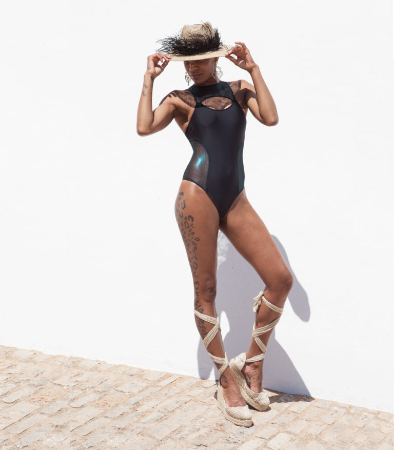 Reminiscent of '90s swimsuit styles, the 'Nieves' one-piece swimsuit has a high leg cut to give the illusion of longer legs and mesh side panels. This sophisticated design created in black sculpting black stretch fabric with a high halterneck and the straps keep the neck and back securely in place Handmade in Ibiza